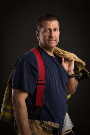 sholders: Firefighter Off Duty Standing portrait on dark Background Stock Photo