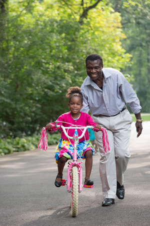 grand kid: Smiling African American Man Helping Little Girl Biking Outdoor, grandpa and grand daughter Stock Photo