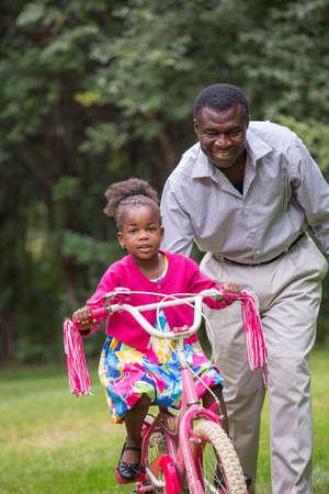 grand kid: Smiling African American Man Helping Little Girl Biking Outdoor