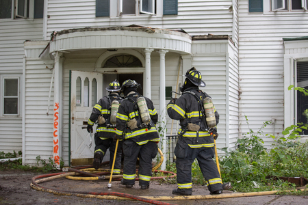 Three Firefighters on Fire Scene Walking into a building Editorial