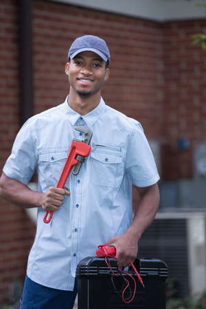 Smiling Young African American  Worker Holding Toolbox and Wrench Standing in front of AC Unit photo