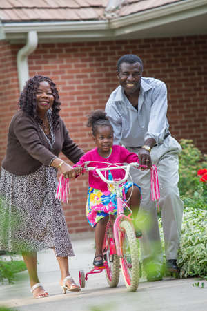 grand kid: Smiling African American Grand Parents Helping Little Girl Biking Outdoor, grandpa and grand daughter