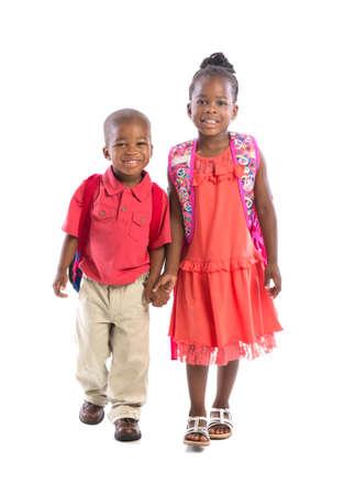 school backpack: Sonriente joven mujer afroamericana hermano y hermana de la mano aisladas sobre fondo blanco con mochila caminando