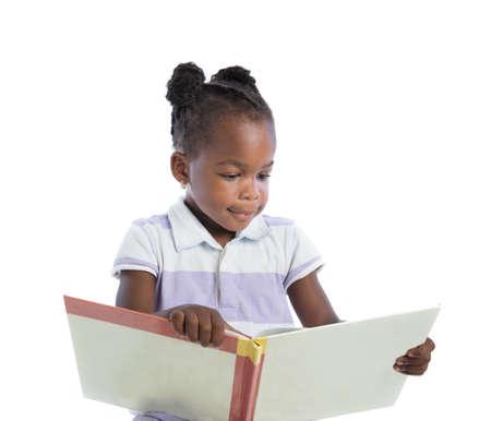 niños leyendo: Cuatro Años de Edad afroamericano Muchacha que lee el libro aislado en el fondo blanco Foto de archivo
