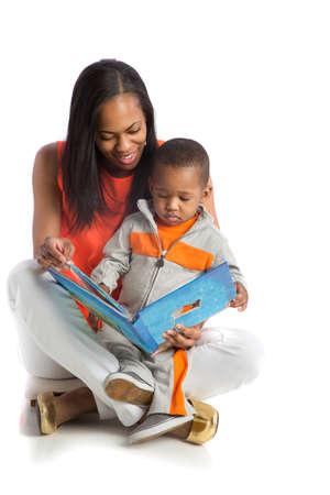 parent and child: Sonriendo la madre del afroamericano y beb� libro de lectura juntos en fondo blanco aislado