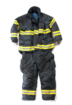 A paire of used worn firefighter pants and suit isolated on white background Imagens