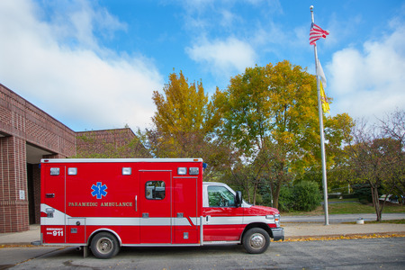 Paramedic Ambulance outside Firefighter Station under blue sky