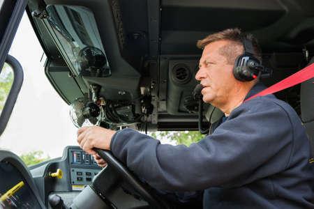 camion de bomberos: Conductor del coche de bomberos del bombero con el auricular en el interior Comandante Veh�culo Foto de archivo