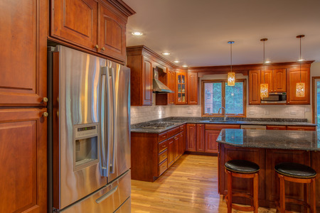 cornor newly finished kitchen with granite counter top hardwood cabinet and floor stainless steel fridge Imagens