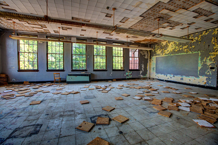 dusty abandoned classroom with falling ceiling tiles and broken chalk board