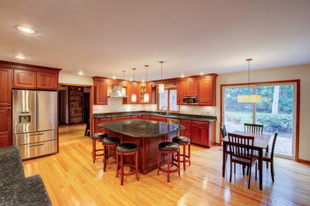 hoek nieuw afgewerkte keuken met granieten aanrechtblad hardhouten kast en de vloer RVS koelkast Stockfoto