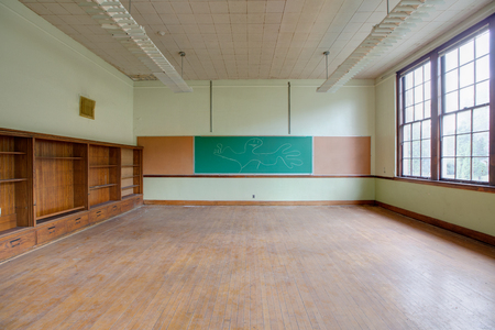 dusty ababdoned classroom with bookshelf and chalk board