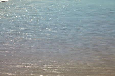 Seafoam bubbles closeup with water edge on a sandy beach.