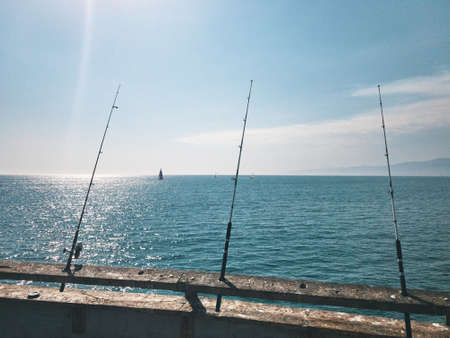 Fishing rods are waiting for biting on the pier. Against the background of sailing yachts. A warm summer day in California., USA Imagens