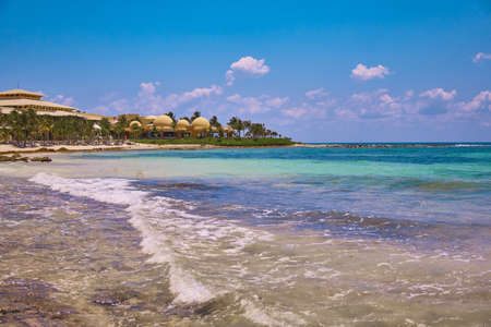 View at luxury resort hotel beach of tropical coast. Leaves of coconut palms fluttering in wind against blue sky. Turquoise water of Caribbean Sea. Riviera Maya Mexico