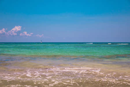 View of tropical beach. Tourists ride parasailing boat with parachute. Sailing yacht sails on waves. Turquoise water of the Caribbean Sea. Riviera Maya Mexico.