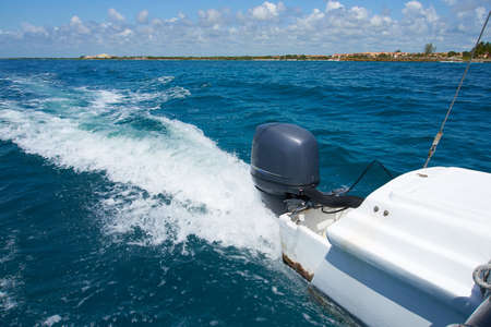Trail on water surface behind of fast moving motor catamaran in the Caribbean Sea Cancun Mexico. Summer sunny day, blue sky with clouds.