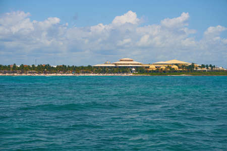 View of the shore from the boat on the waves in the warm Caribbean Sea. Riviera Maya Mexico. Summer sunny day, blue sky with clouds. Imagens