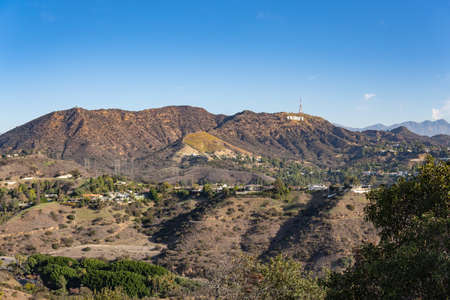 View of Hollywood Sign from Hollywood Hills. Warm sunny day. Beautiful clouds in blue sky. Banco de Imagens