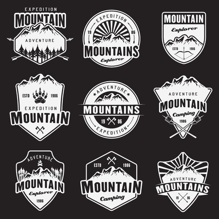 Mountain travel, outdoor adventure, camping and hiking set of white vector emblems, labels, badges and logos isolated on dark background