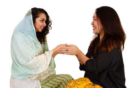 2 Malaysian ladies in traditional dress shaking hands