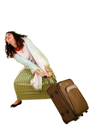 Malaysian lady in traditional dress pulling luggage