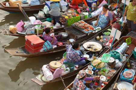 Boats filled with food or tourists at the Ampawa Floating Market in Thailand.