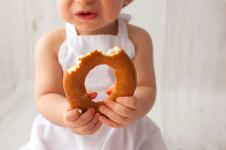 Cute ten months old baby boy holding a bagel, close-up.