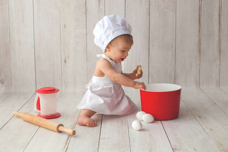 Cute ten months old baby boy, in a suit of a cook, sits on a light wooden background. Chefs hat on his head. He is a bakery cook.