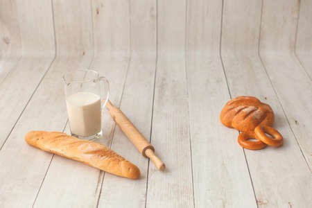 Photo shoot for little cook. Bread and bagels on wooden background.