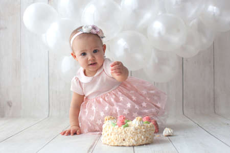 One year old baby celebrates birthday. Photo zone with ballon. Cute dress in pink color.