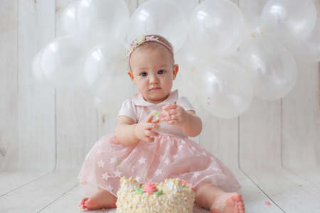 One year old baby celebrates birthday. Photo zone with ballon. Cute dress in pink color. Archivio Fotografico