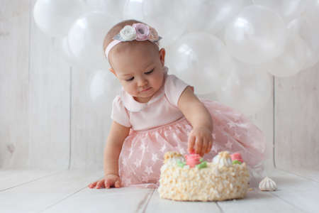 One year old baby celebrates birthday. Photo zone with handmade colorful paper flags. Cute dress in pink color.