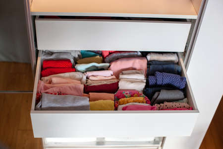 Vertical storage of clothing. Clothing folded for vertical storage in the linen drawer. Nursery. Sliding wardrobe. Room interior. Neatly folded clothes in chest of drawers.