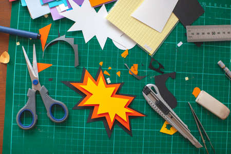 Workplace for paper craft. Progress with paper art, cutting on green cutting mat. Banco de Imagens