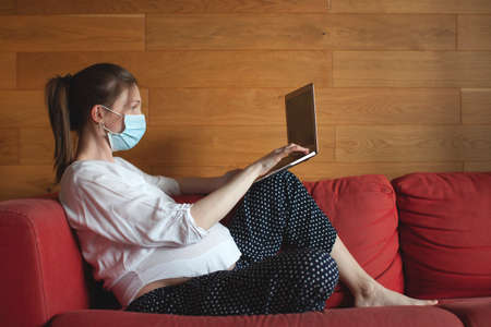A pregnant young woman works at home. Stay at home. Online education. Wearing a face mask. Imagens