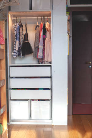 Vertical storage of clothing. childrens room. Clothing folded for vertical storage in the linen drawer. Nursery. Sliding wardrobe. Room interior. Neatly folded clothes in chest of drawers. 版權商用圖片