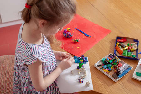 7 years old baby craft with plasticine in the kitchen. Home interior. Home education.