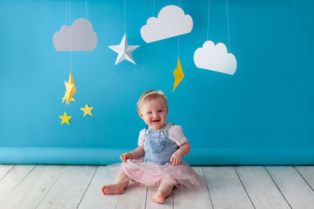 One year old baby celebrates birthday. Photo zone. Cute dress in white color. She touches a paper yellow star. Imagens