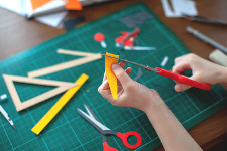 A five-year-old girl cuts out with a scissors yellow paper, craft with kids, cut, hobby, free time.
