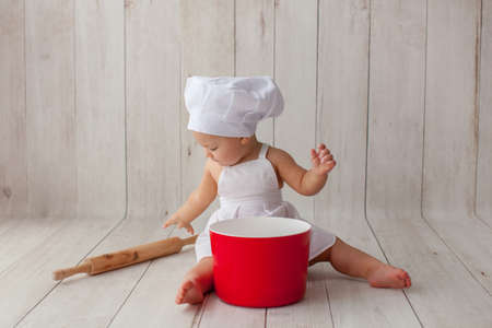 Little chef in apron and a suit of a cook, sits on a light wooden background. Chefs hat on his head. He is a bakery.