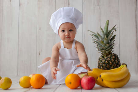 Cute one year old girl in apron is sitting in the photo zone. Birthday photoshoot and smash cake party. She eat fruits. Pineapple, orange and apple on a wooden background. Little chef.