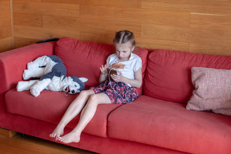 Seven year old girl sitting on the couch and playing on the phone. Home interior.