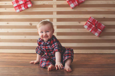 One year old baby girl sitting on wooden background. Smash cake photo shoot. Gift. Holiday inspiration.