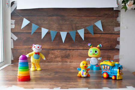 Background for one year old baby photo shoot. Paper garland on wooden backdrop with toys. For little boys and girls.