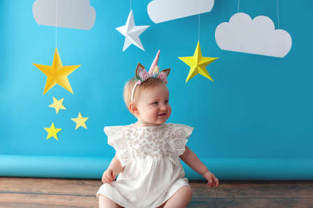 One year old baby celebrates birthday. Photo zone. Cute dress in white color. She touches a paper yellow star.