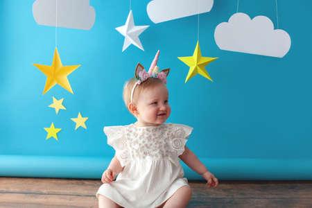 Un bébé d'un an fête son anniversaire. Espace photos. Jolie robe de couleur blanche. Elle touche une étoile jaune en papier.