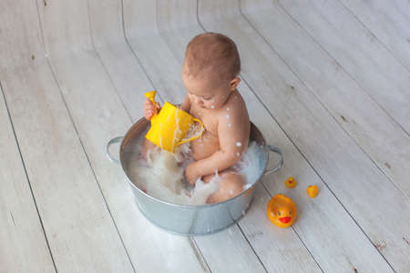 Little baby girl takes bath with yellow rubber duck.