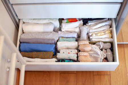 Vertical storage of clothing. Clothing folded for vertical storage in the linen drawer. Nursery. Sliding wardrobe. Room interior. Neatly folded clothes in chest of drawers. Newborn baby clothes. Foto de archivo