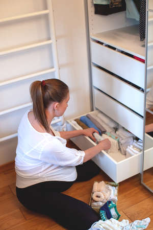 Vertical storage of clothing. A pregnant girl is preparing for the birth of a child. She takes apart the clothes. Room interior. Neatly folded clothes in chest of drawers. Newborn baby clothes.